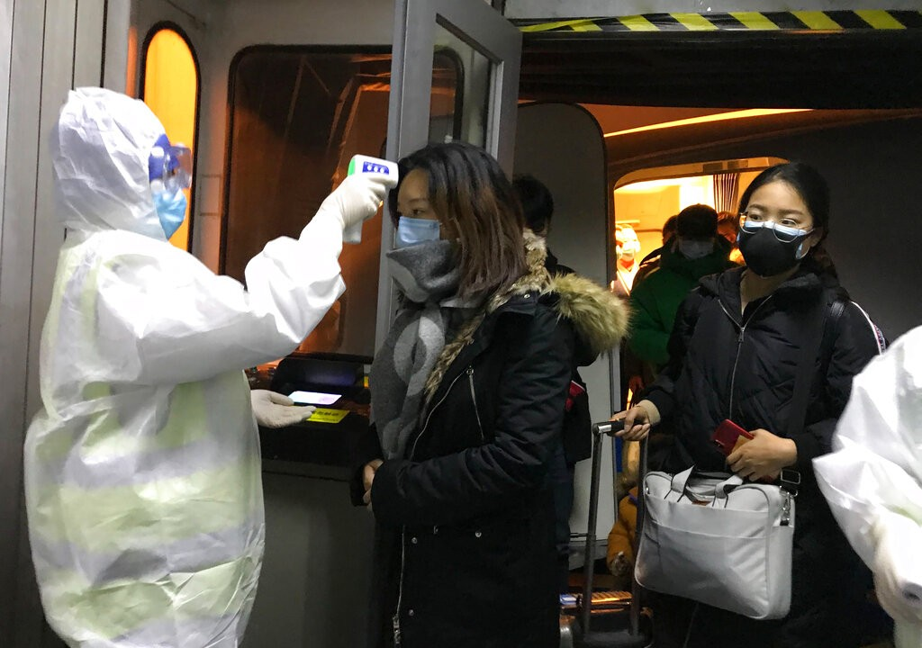 北京首都國際機場全面為來自武漢市的旅客進行體溫檢疫。(圖/美聯社)
