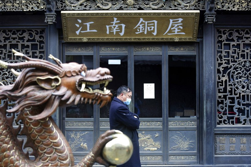 A man wears a face mask as he walks past a closed tourist attraction in Hangzhou in eastern China's Zhejiang Province.