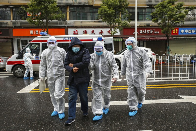 Medical workers in protective gear help patient in Wuhan.