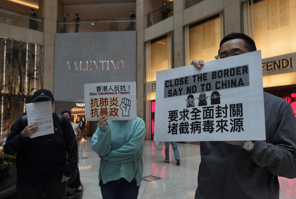 """Protesters hold placards that read """"Close the border, say no to China"""" at a mall in Hong Kong on Tuesday (Feb. 4)."""