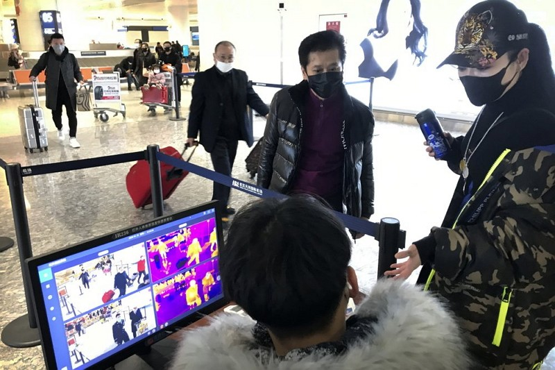 In this Jan. 21, 2020, file photo, travelers pass through a health screening checkpoint at Wuhan Tianhe International Airport.