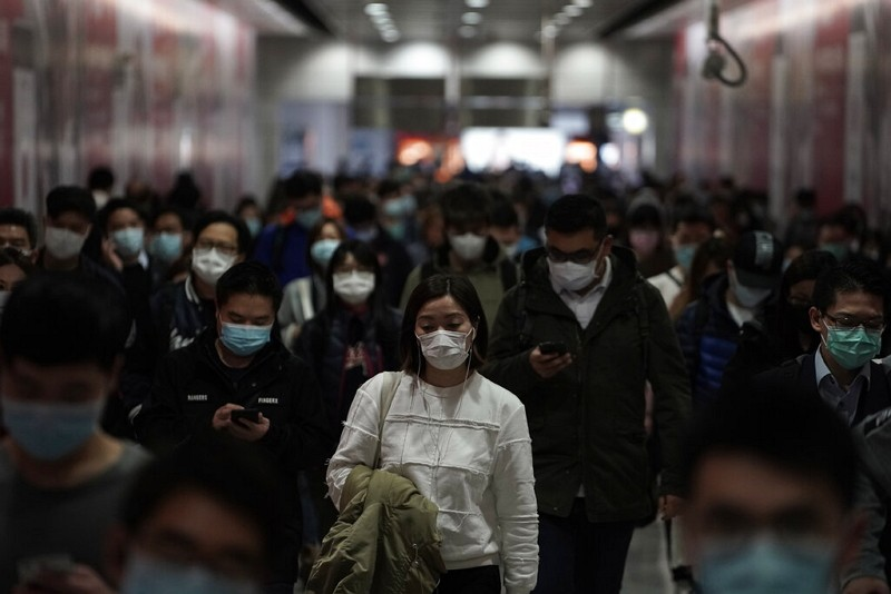 People wearing masks walk in a subway station in Hong Kong.