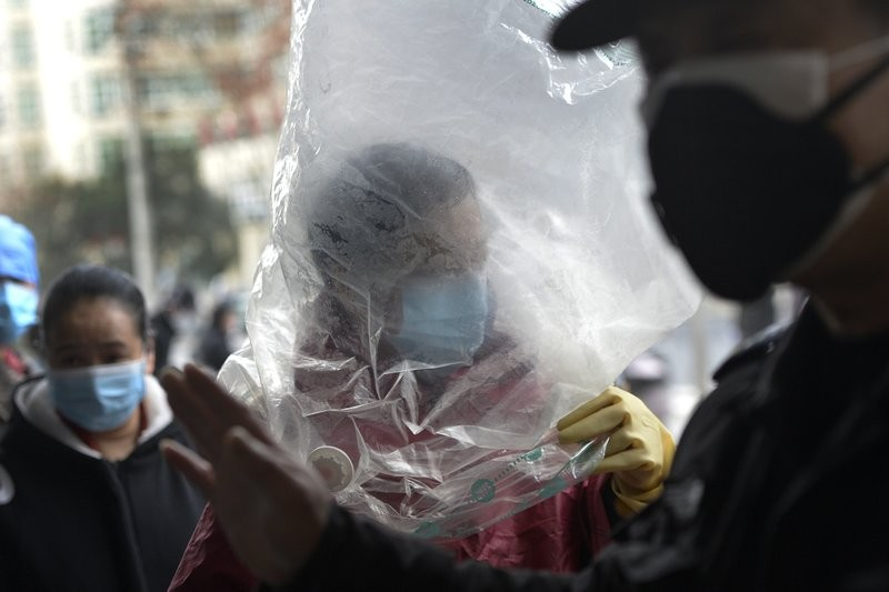 A man wearing a protective face mask covered himself with a plastic cover before enters a supermarket in Wuhan in central China's Hubei province, ...
