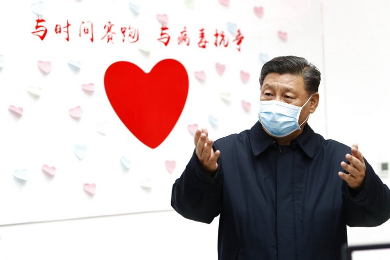 "Xi Jinping gestures by slogan reading: ""Race against time, fight the virus."""