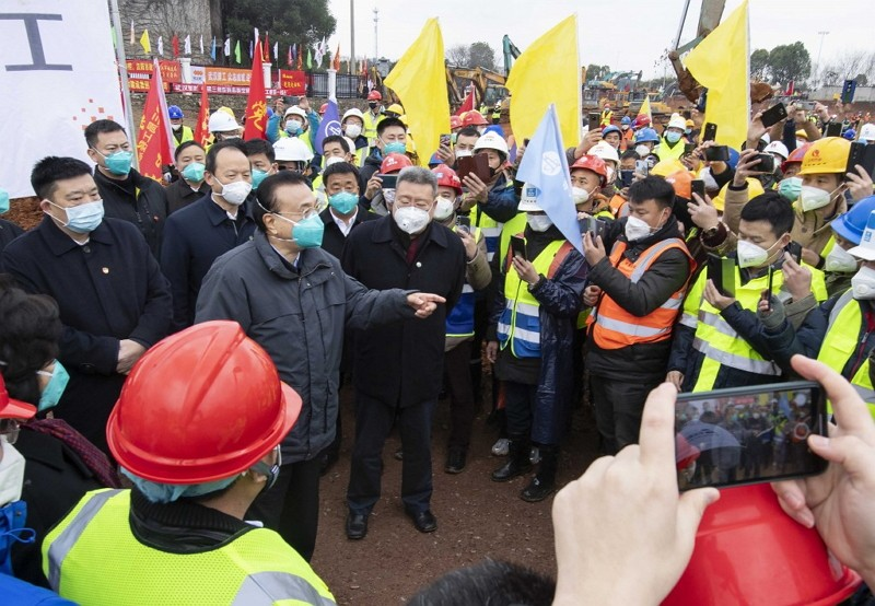 Premier Li Keqiang, fourth left, speaks with construction workers at the site of makeshit field hospital being built in Wuhan.