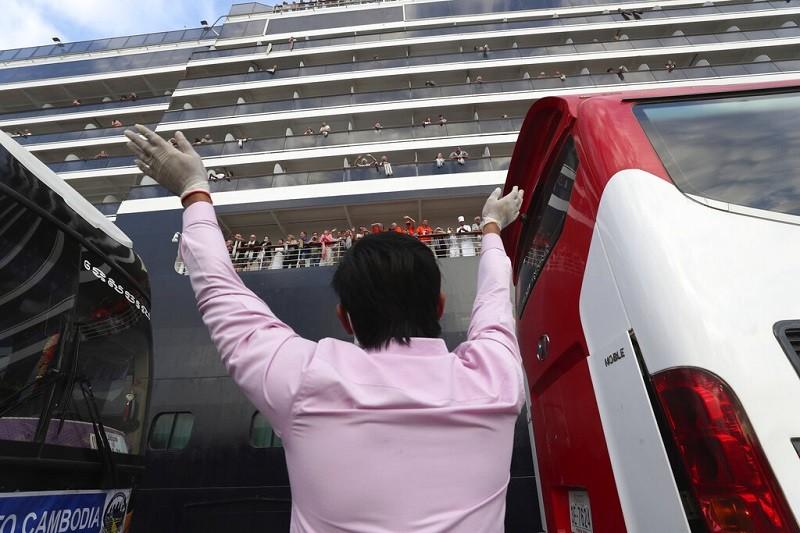 一名男子14日向停靠在西哈努克港的威士特丹號郵輪旅客打招呼 (美聯社)