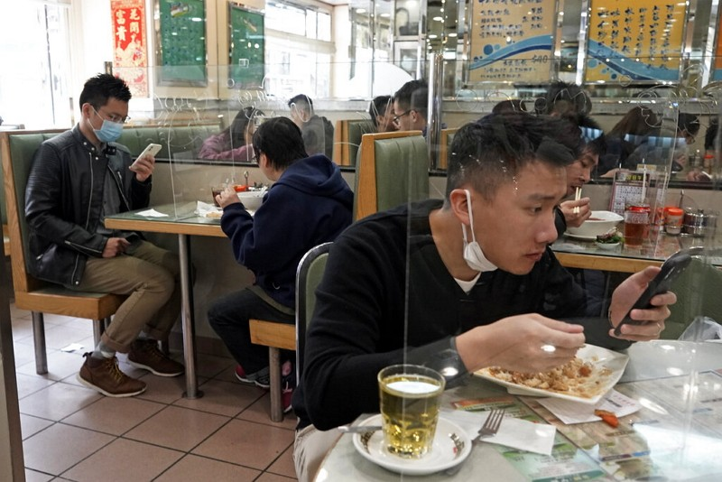 Customers have lunch with a transparent plastic panel setup on the table in Hong Kong.