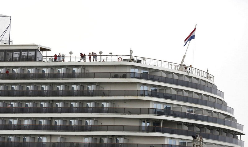 Passengers stand on the top deck of the MS Westerdam while the cruise ship is docked in Sihanoukville, Cambodia.