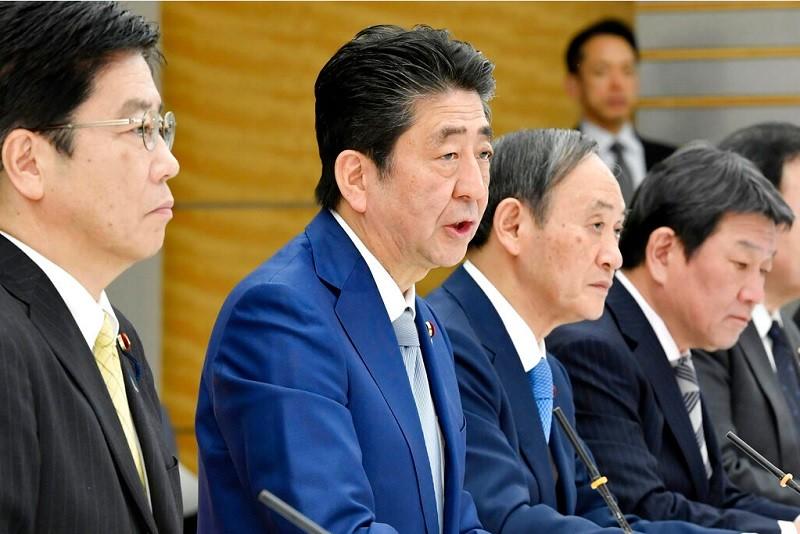 圖為日相安倍(左2) 13日出席內閣因應武漢肺炎相關會議 (美聯社)