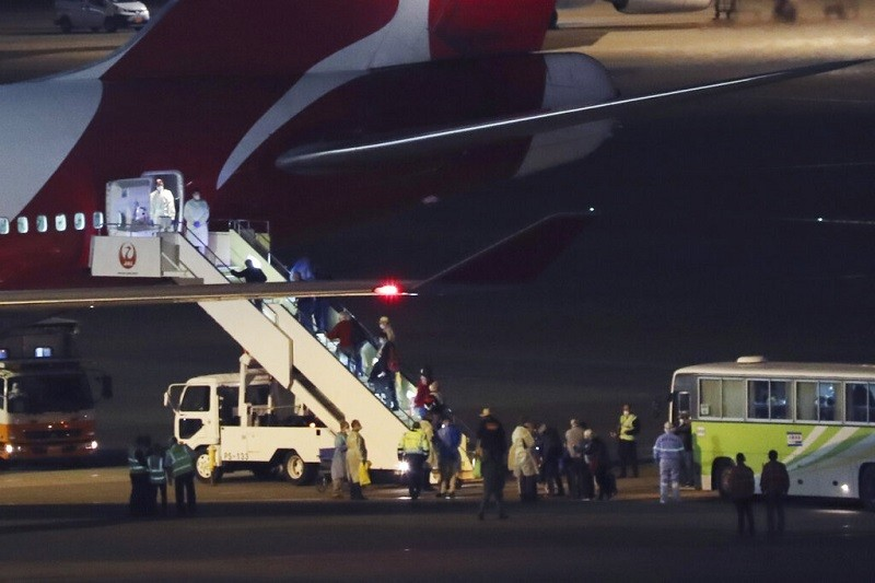 圖為19日鑽石公主號旅客解除隔離後, 在羽田機場搭機返鄉情形 (美聯社)