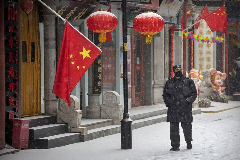 A security guard wears a face mask as he walks along a pedestrian shopping street during a snowfall in Beijing.