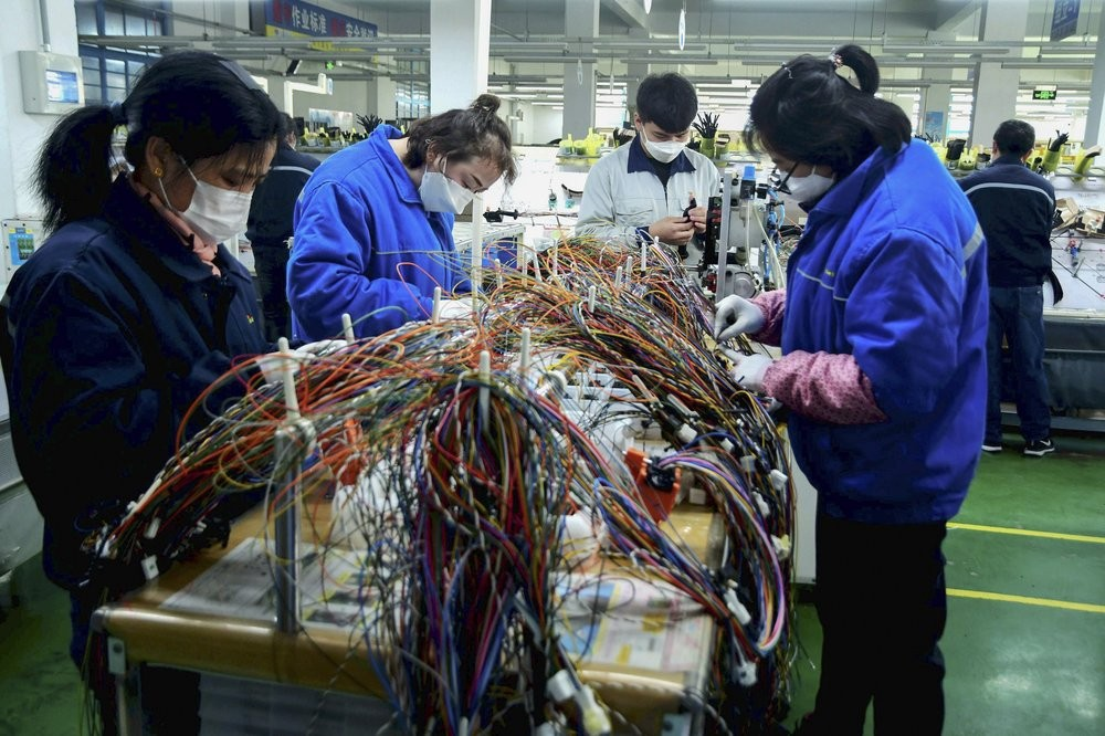 Masked workers assemble wiring for automobile at factory in Qingdao, China