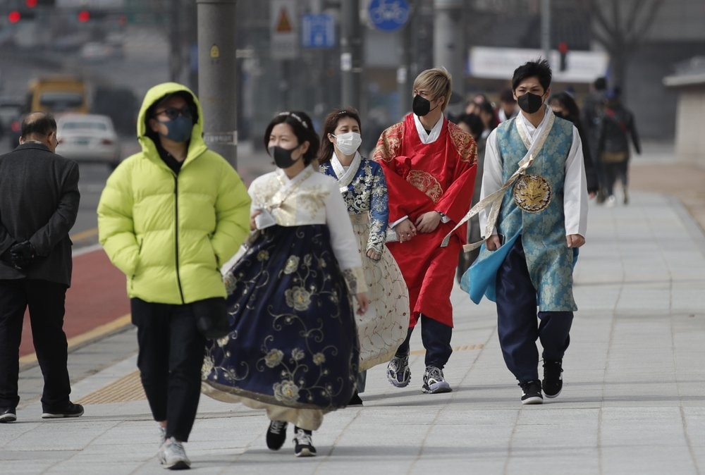 Koreans in traditional dress wearing face masks in Seoul