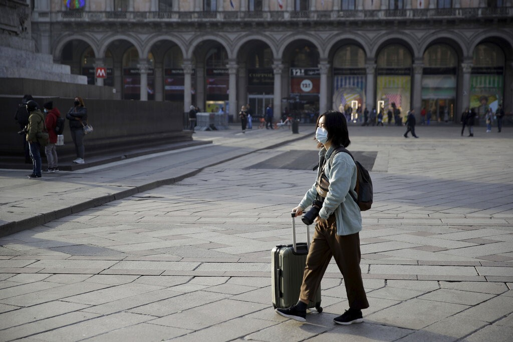 A woman wearing a sanitary mask pushes a trolley in Milan on Feb. 23.