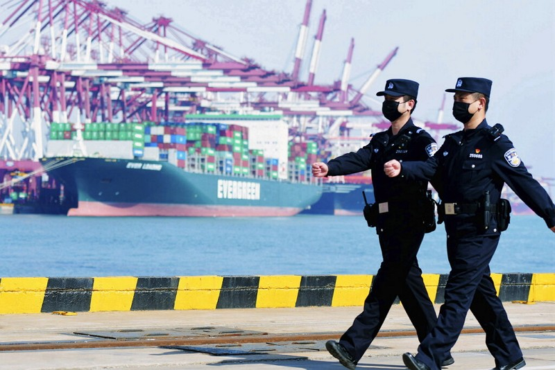Police officers wearing face masks patrol at a container port in Qingdao.