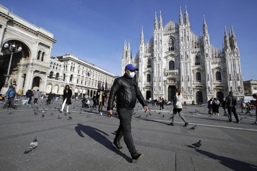 A man wearing a mask in front of the Duomo cathedral in Milan