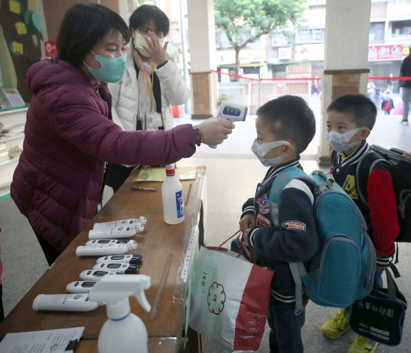 Staff taking temperatures of students at Taipei's Fude Elementary School.