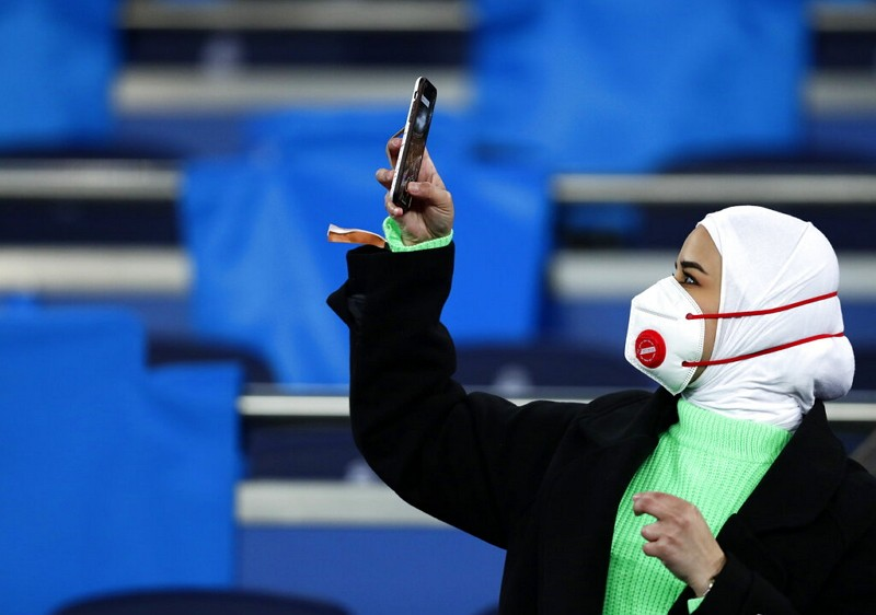 A fan wearing a protective mask takes a picture with her cell phone prior the Champions League.