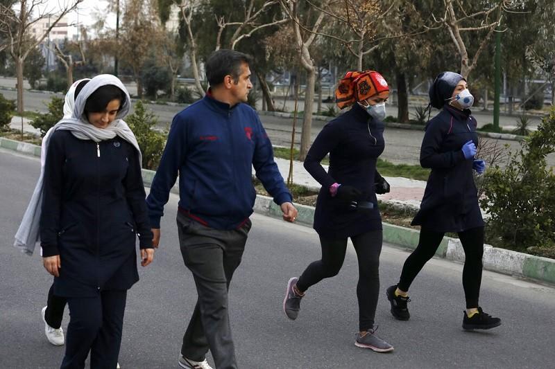 武漢肺炎陰影下, 28日在伊朗首都德黑蘭一處公園, 有民眾全副武裝,也有人一派輕鬆 (美聯社)