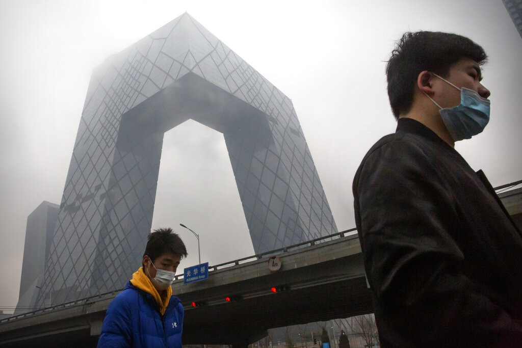 People wear face masks as they walk past the China Central Television (CCTV) Building in Beijing.