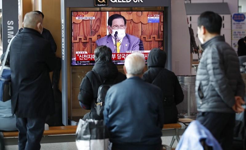 圖為2日南韓民眾在首爾火車站, 觀看戴著口罩的新天地教主李萬熙, 召開記者會的電視畫面 (美聯社)