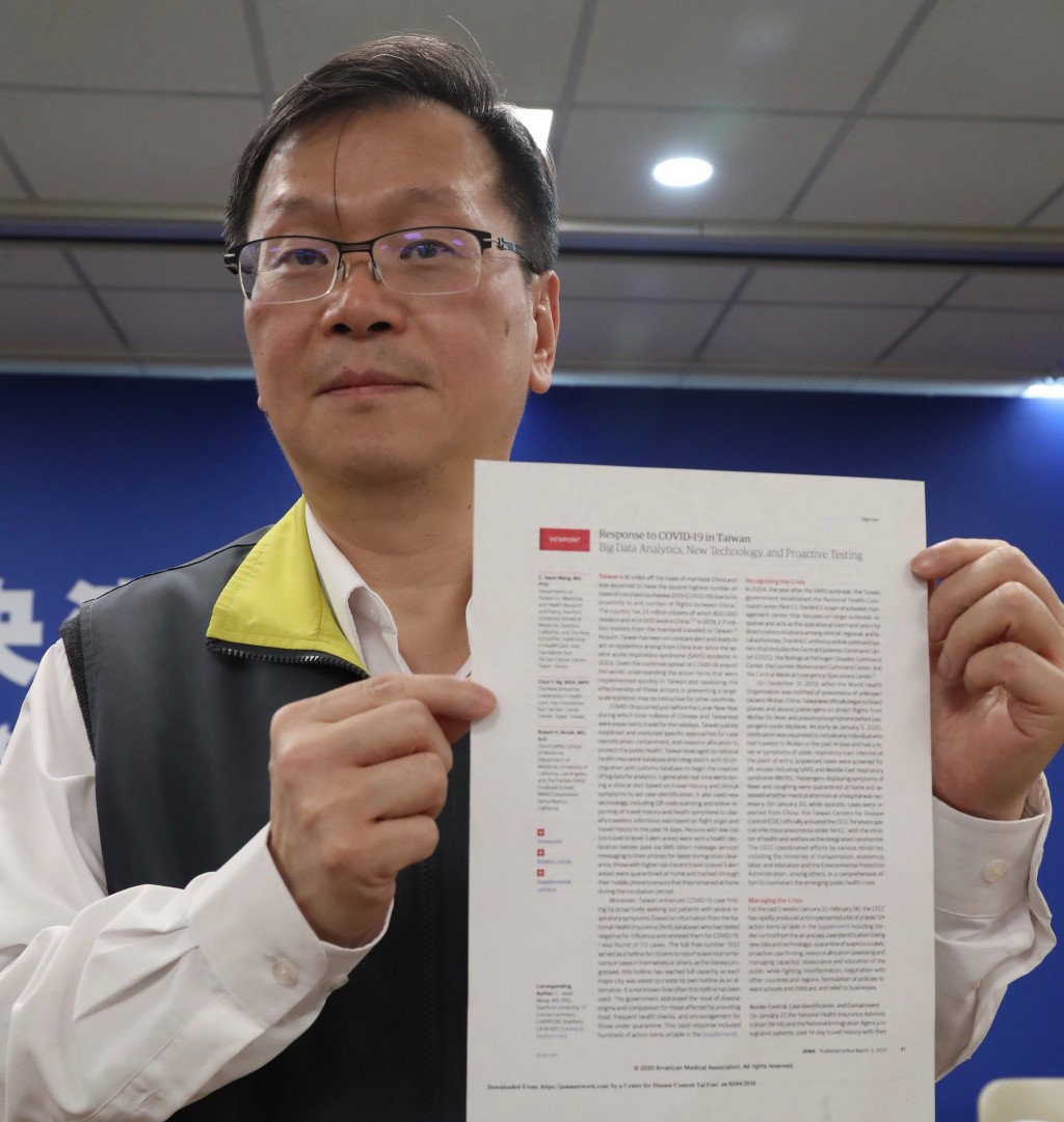 Taiwanese health official shows JAMA article to the media.