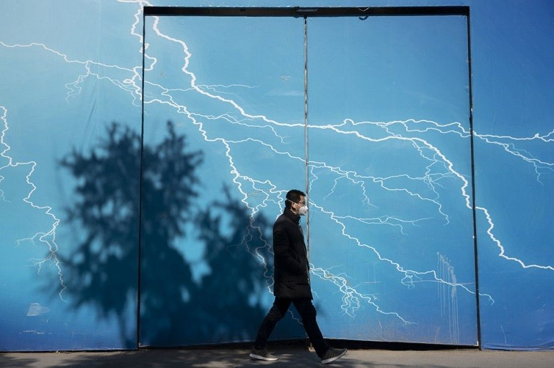 A man wearing a mask walks past a billboard depicting lightning in Beijing on Wednesday, March 4, 2020.