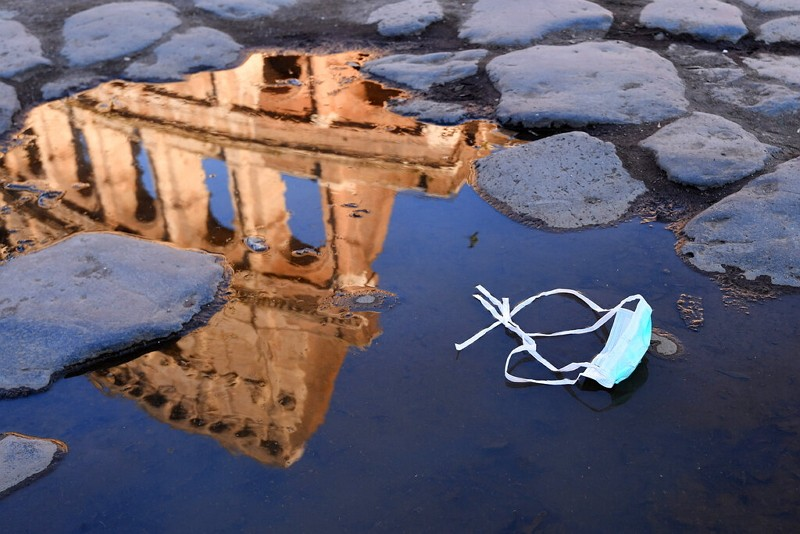 The Colosseum in Rome reflected in a puddle where a face mask was left.