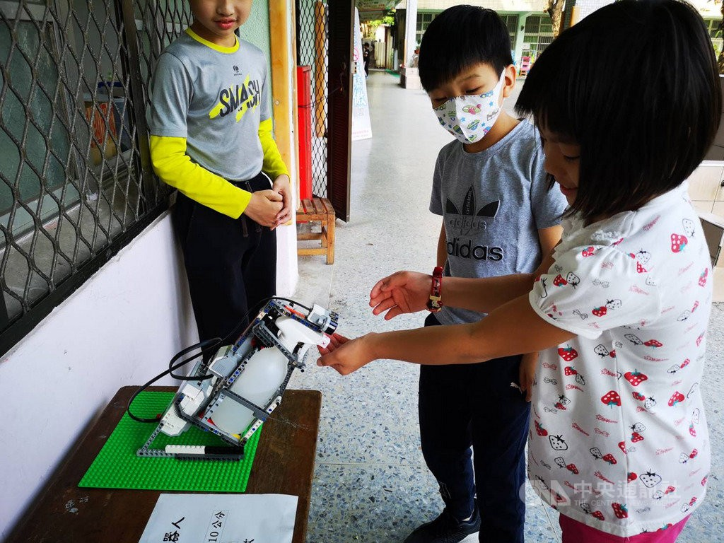 Student getting sprayed by robot. (Kaohsiung Education Bureau photo)