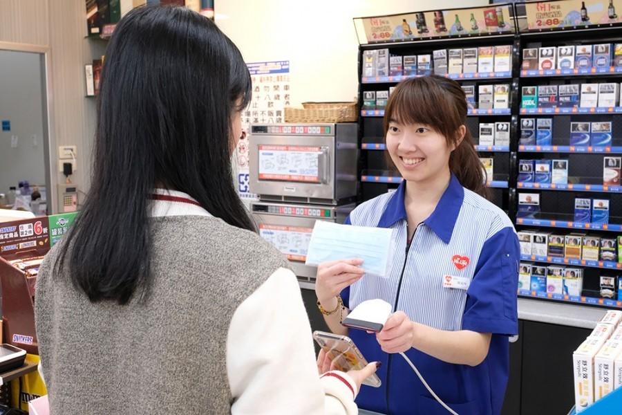 Hi-Life clerk handing masks to customer. (Hi-Life photo)