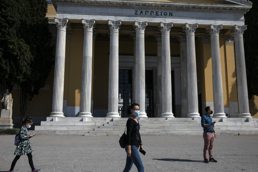Tourists wearing protective masks walk in front of Zappeion in Athens.