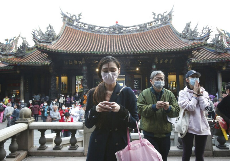 People wear face masks to protect against the spread of the coronavirus as they pray at the popular Longshan Temple in Taipei.