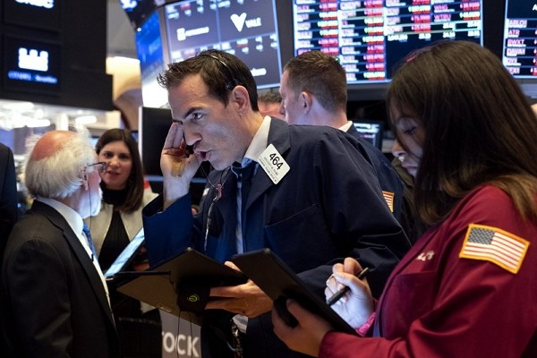 Trader Gregory Rowe, center, and others work on the floor of the New York Stock Exchange Monday, March 16, 2020.