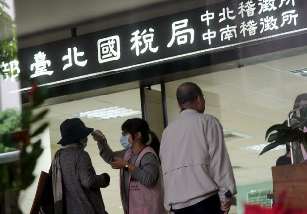 Woman having her temperature checked outside of Taiwan's Tax Bureau.