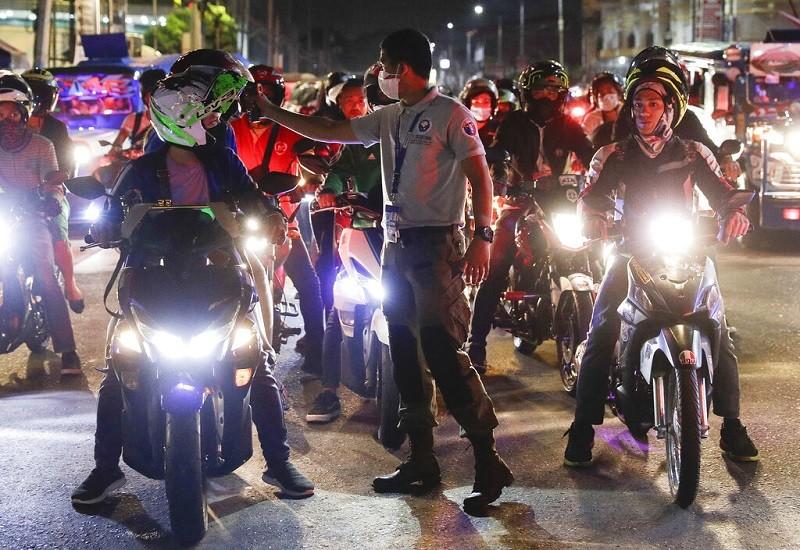 菲律賓為了預防疫情擴散, 在首都馬尼拉設置檢查站, 一名交通警察正在幫騎士量體溫 (美聯社)