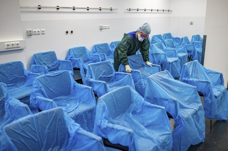A nurse assembles plastic-wrapped chairs in a waiting area in the central emergency room of the University Hospital in Essen, Germany, Monday, March 2...