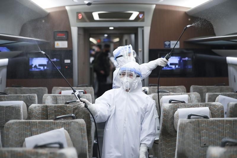 中國在北京實施最嚴格的防疫措施,圖為消毒人員在高鐵車廂作業。(中新社提供)中央社