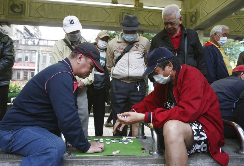 Group of men wear face masks to protect against coronavirus while playing Chinese chess in Taipei.