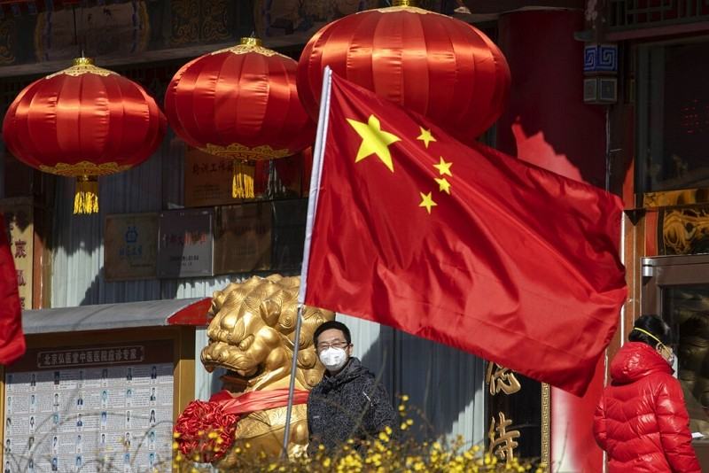 A masked man looks out near a national flag outside a traditional medicine hospital in Beijing.