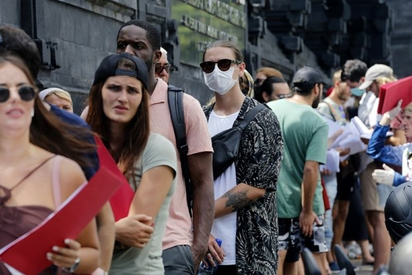 Foreign tourists who are unable to fly home due to the new coronavirus outbreak, queue up outside an immigration office to extend their visas in Bali,...