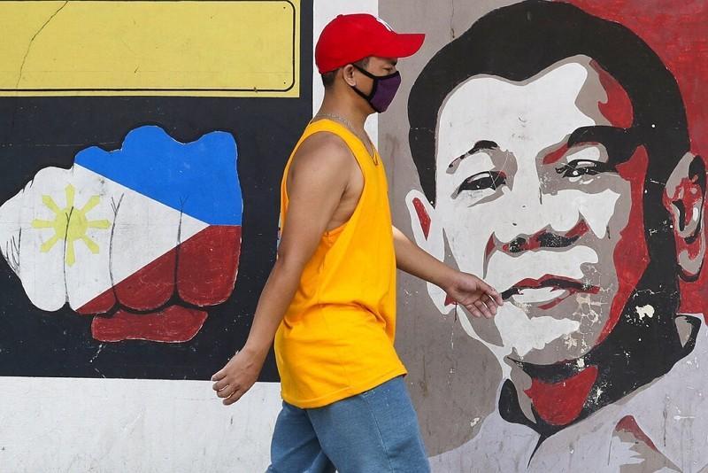 馬尼拉街頭,背景為總統杜特蒂頭像(圖/美聯社)