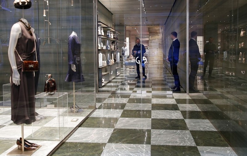 Two shop assistants wait for customers at a fashion store in Monte Napoleone shopping street in Milan, Italy.