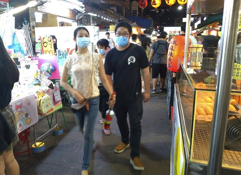 People wear face masks to protect against the spread of the coronavirus and visit at a night market in Taipei.