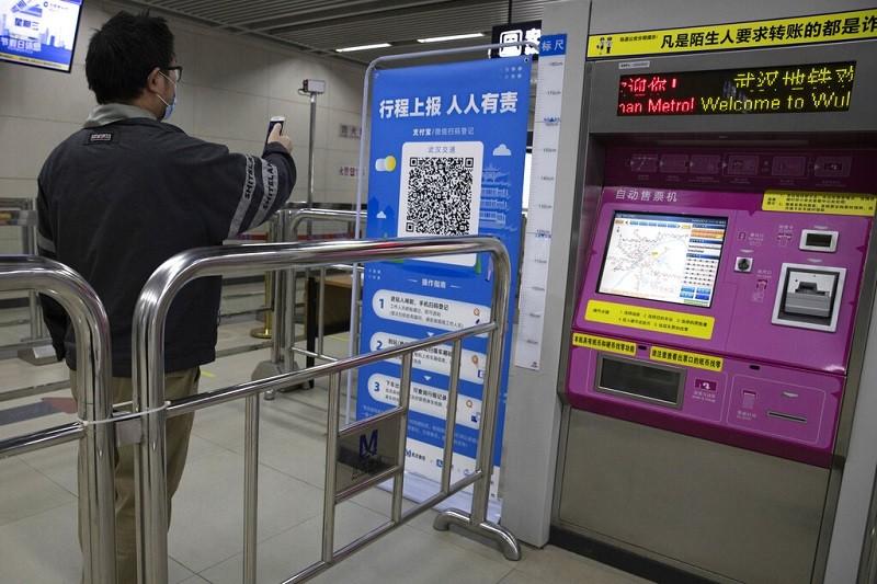圖為4月1日一名乘客用手機掃瞄武漢地鐵站的QR Code, 以便取得獲准進站的「綠燈」。(美聯社)