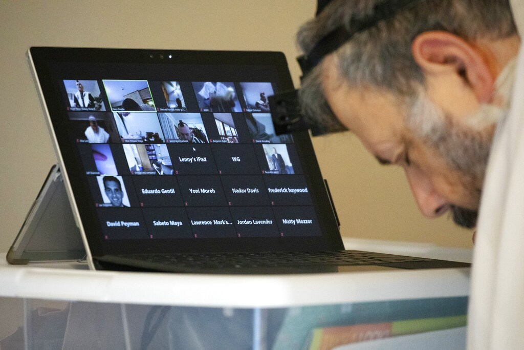 The photo shows a man attending a Zoom meeting through hiselectronic tablet.