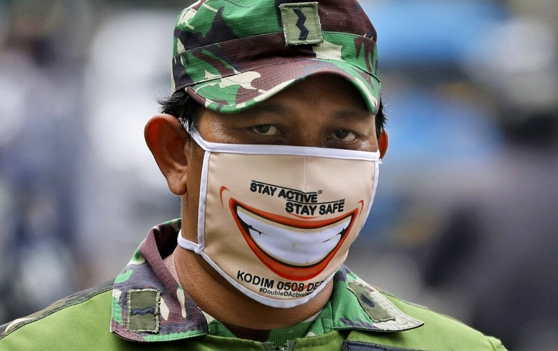 An Indonesian soldier wears face mask as he and his team man a checkpoint in Jakarta.