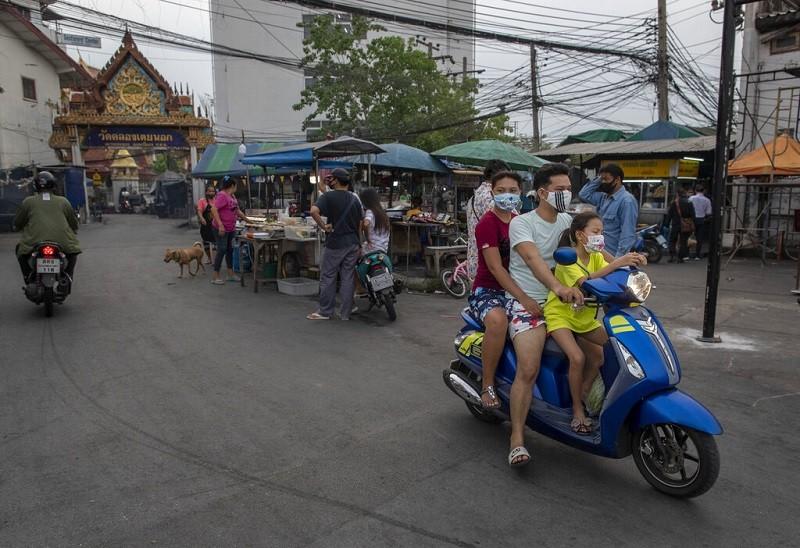 圖為泰國街頭戴口罩的一家人(美聯社)