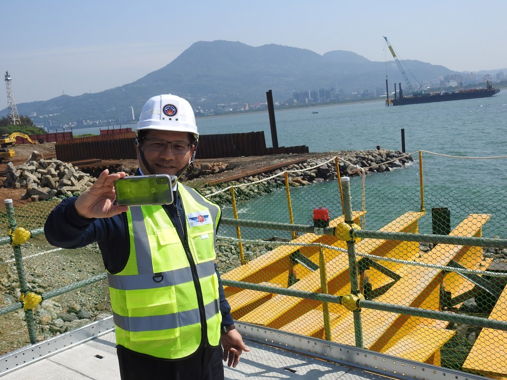 Transportation Minister Lin Chia-lung taking a selfie with the Tamkang Bridge construction site and the Guanyin Mountain