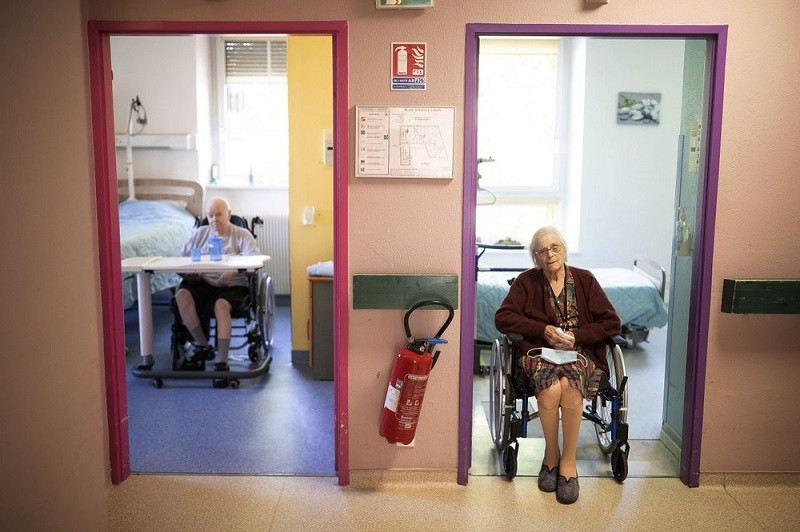 Marie Lithard, right, and her neighboor Yves Chretien sit looking out of their rooms in a nursing home in Ammerschwir, France Thursday April 16, 2020....