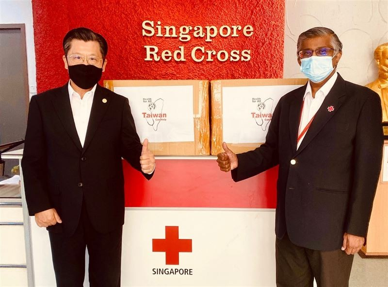 Liang (left), William (right), stand in front of two boxes from shipment of 100,000 masks. (TRO photo)